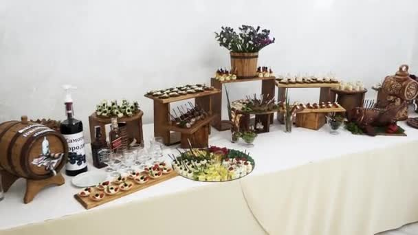 A large, beautiful, bright buffet with many meat snacks is on a white table and is waiting for guests at the celebration. View from above.