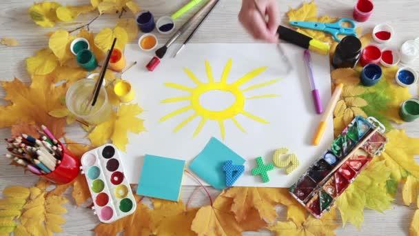 Podzimní javorové listy na stole a kartáč kreslení slunce