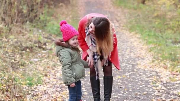 Matka a dcera hraje třít nosy v podzimním lese