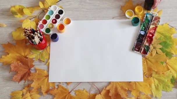 Autumn leaves and objects to paint on a wooden background