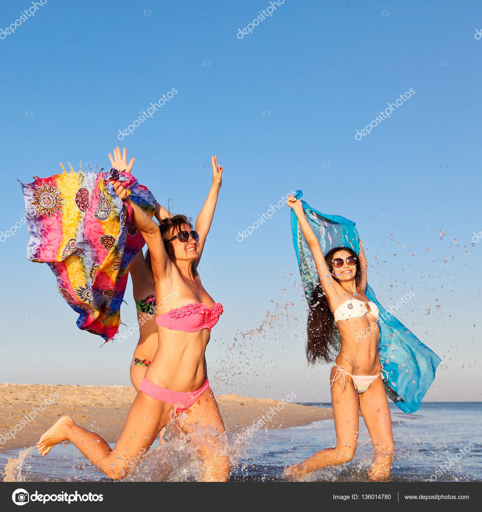 5955cb77b4f88 Three beautiful young women in bathing suits and sunglasses fun jumping on  the shore of the Red Sea waving colored fabrics — Photo by ...