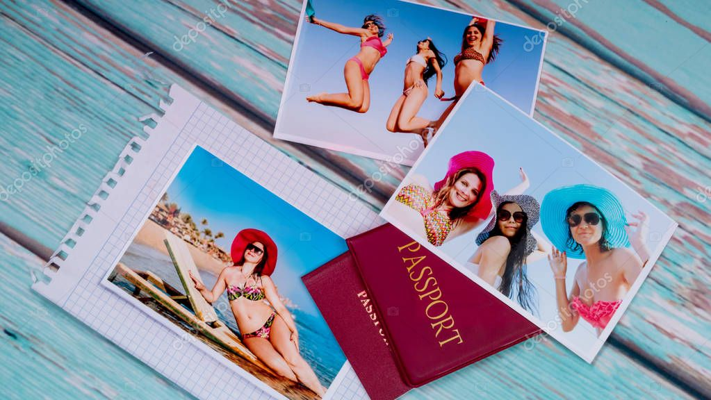 Photos of beautiful girls on the beach and passports on a wooden table