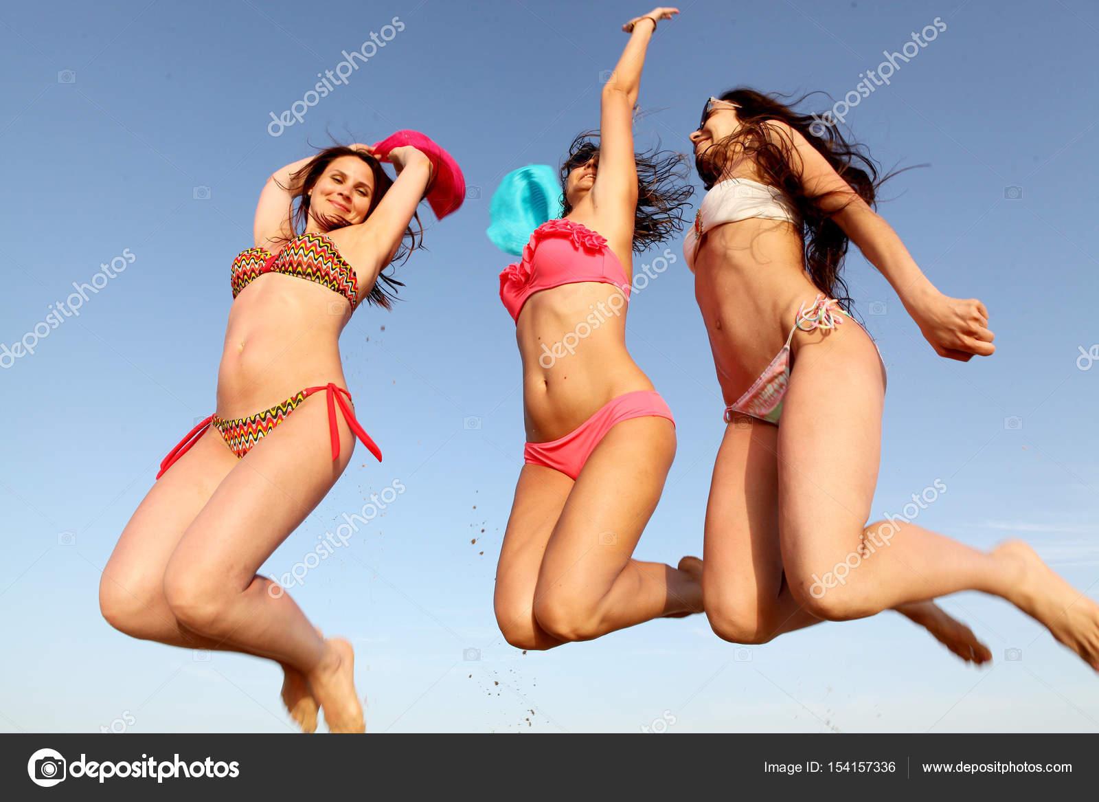 Salto di giovani ragazze in costume da bagno sulla spiaggia — Foto ...