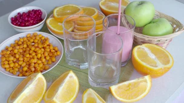 Ovocný koktejl přírodní vitamín jahod se nalije do sklenice na stůl s pomeranče a rakytníku. Detoxikační