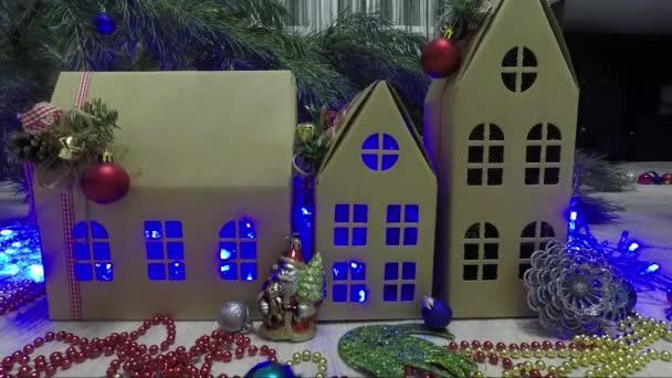 Tři lepenkové domy mezi věnce a vánoční koule. Nový rok. Vánoční
