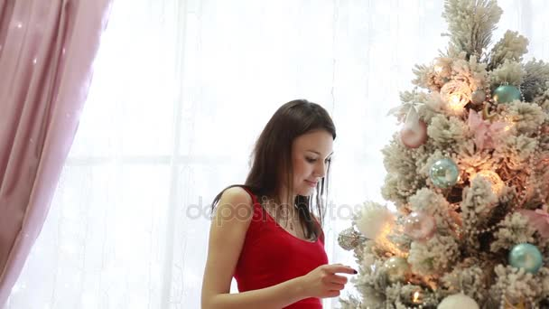 Beautiful girl close up decorating a Christmas tree in the interior