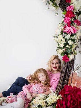 Mom and daughter in embrace with flowers. Spring