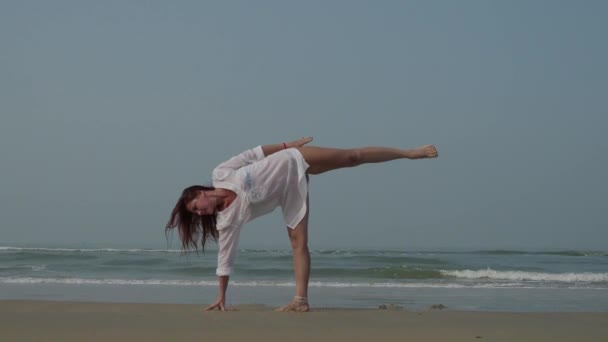 A beautiful girl is practicing yoga on the beach. 4K