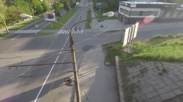 pohled z mostu na křižovatku s pěší křižovatkou, lidé projít a auta řídit