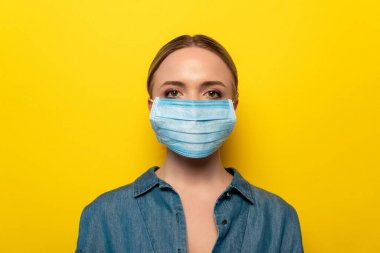 young woman in medical mask on yellow background, coronavirus concept