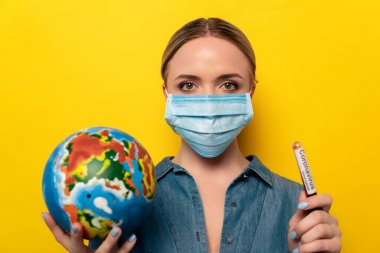 Young woman in medical mask holding test tube with coronavirus blood sample and globe on yellow background stock vector