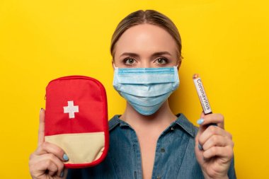 Young woman in medical mask holding test tube with coronavirus blood sample and first aid kit on yellow background stock vector