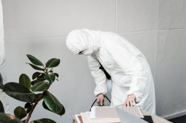 person in white hazmat suit, respirator and goggles disinfecting workplace in office, coronavirus concept