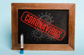 koronavírus felirat írva a táblára a kémcső közelében vérmintával kék alapon