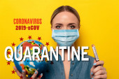 young woman in medical mask holding test tube with coronavirus blood sample and globe on yellow background, 2019-ncov and quarantine illustration