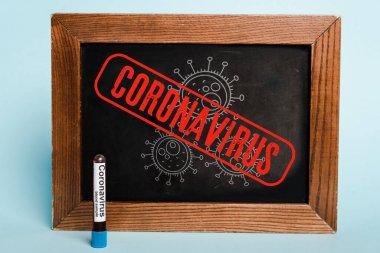 Coronavirus lettering written on chalkboard near test tube with blood sample on blue background stock vector