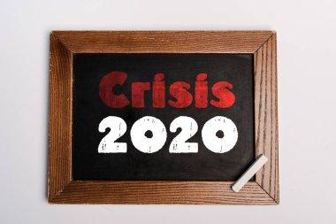 Crisis 2020 lettering written on chalkboard on white background, coronavirus concept stock vector