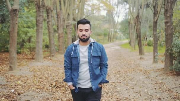 muž kráčí podzimním listím v lese