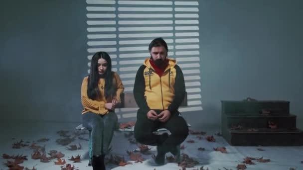 Trauriges junges Paar, das auf einer Bank in die Kamera blickt