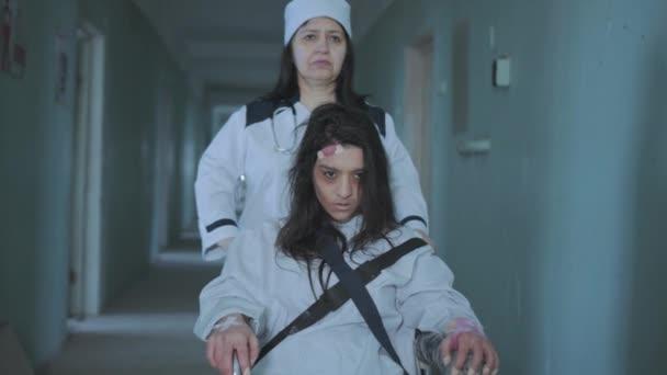 Female Nurse Pushing Patient In The Wheelchair Through The Hospital Corridor