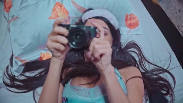 schönes Mädchen im Bett liegend macht ein Foto von ihrem Freund