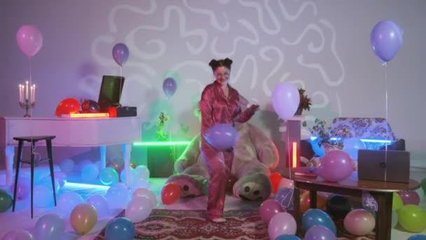lány táncol rózsaszín pizsama van egy kék léggömb a kezét, sokszínű léggömbök a padlón, szoba színes neon fények díszített