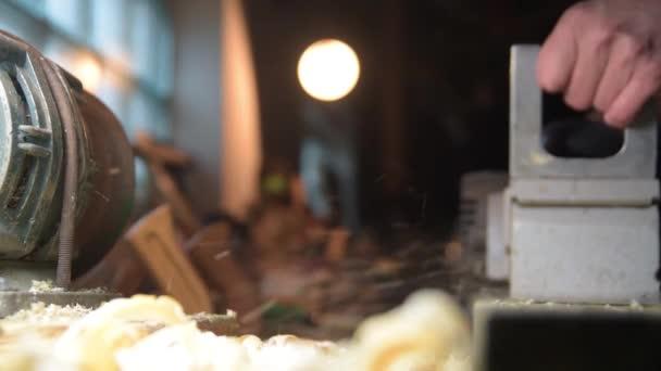 Tesař s elektrickým hoblíkem v dílně. Zpomalený detail