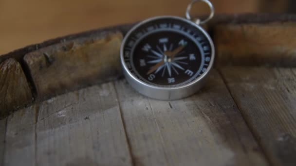 Vintage compass close up on an old wooden barrel