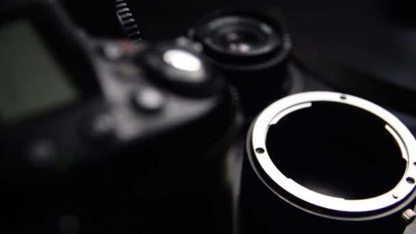 Digital camera, lenses and equipment of the photographer on a dark background