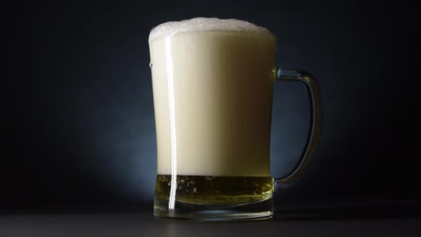 Po stranách přetékajícího pivního džbánu stékaly kapky piva. Zpomalený pohyb a tmavý styl