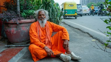 A homeless old man in orange national Indian clothes begs for alms on a Delhi street in India.