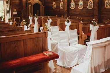 Wooden catholic church interiors. Wedding decorations in rustic chapel. Old vintage religious building indoor architecture.