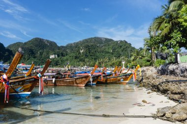 Ko Phi Phi, Krabi, Thailand - November 28 2019: Brown wooden long tail boats on a beach. Ko Phi Phi island in Thailand. Summer vacation landscape.