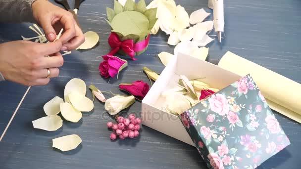 Közeli kép: hullámpapír csapkod élénk rózsaszín női kéz. Női dekoratőr összehajt-ból papír origami virág gombot. Modern művészet: hogy kézműves papír díszíteni, partik, esküvők és március 8.