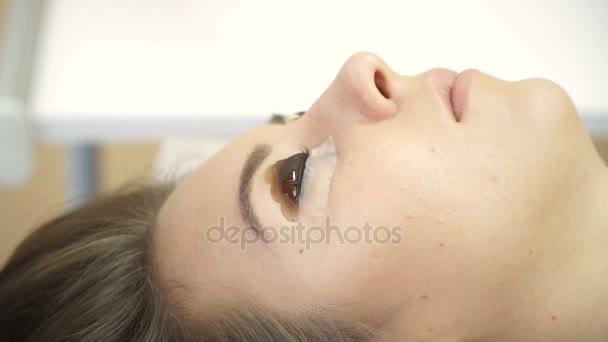 Krásná mladá žena s prodlužování. Barvení a laminace řas. Žena oko s dlouhé řasy. Kosmetika prodlužování řas pro mladou ženu v salonu krásy