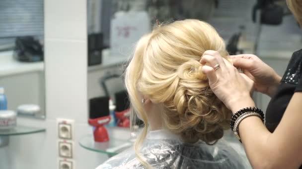 Portrét mladé ženy v salonu krásy: vytvoření nádherné prostředí z kadeře. Blondýnka v kadeřník dělá krásný účes. Vytvoření bitové kopie a péče o vlasy.