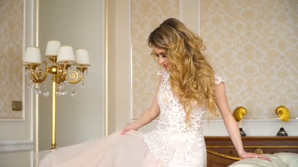 Gyönyörű fiatal menyasszony portréja. Egy lány pózol egy szállodai szobában. A hölgy forog a lány esküvői ruha