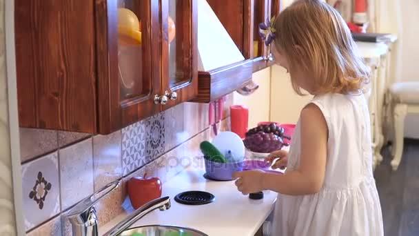 Aktivní malé předškolní věk dítěte, roztomilé batole dívka s blond kudrnaté vlasy, ukazuje hraní kuchyně, ze dřeva, hraje v kuchyni