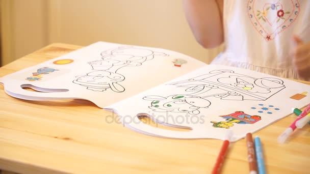 Aktivní malé předškolního věku dítě, roztomilé batole dívka s blond kudrnaté vlasy, kreslení obrázek na papír pomocí barevné tužky a fixy, sedící na dřevěný stůl uvnitř doma nebo mateřské školy
