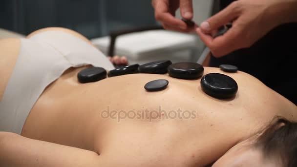 Mladá žena se těší horká masáž v salonu spa jako teplo čedičové kameny jsou umístěny na její svaly