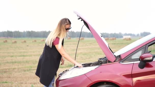 Tenká blondýna dospívající vytáhne Měrka oleje v její motor auta zkontrolovat úroveň maziva