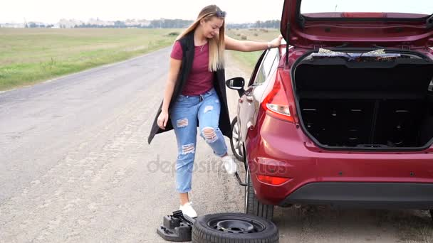 Sexually dressed woman rolling spare wheel on road