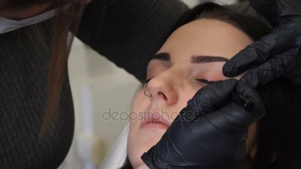 Zblízka střílel. Profesionální specialista na permanentní make-up vyrovnávací oční linky před zákrokem. Krása, make-up a módní koncept