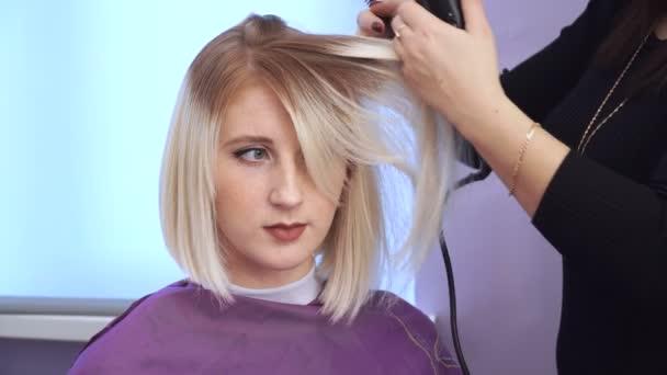 Kadeřník vyhladí vlasy krásné mladé dívky. narovnávání vlasů
