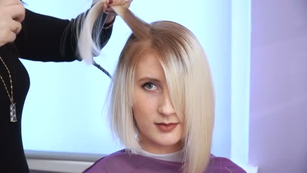 The hairdresser smoothes the hair of a beautiful young girl. hair straightening