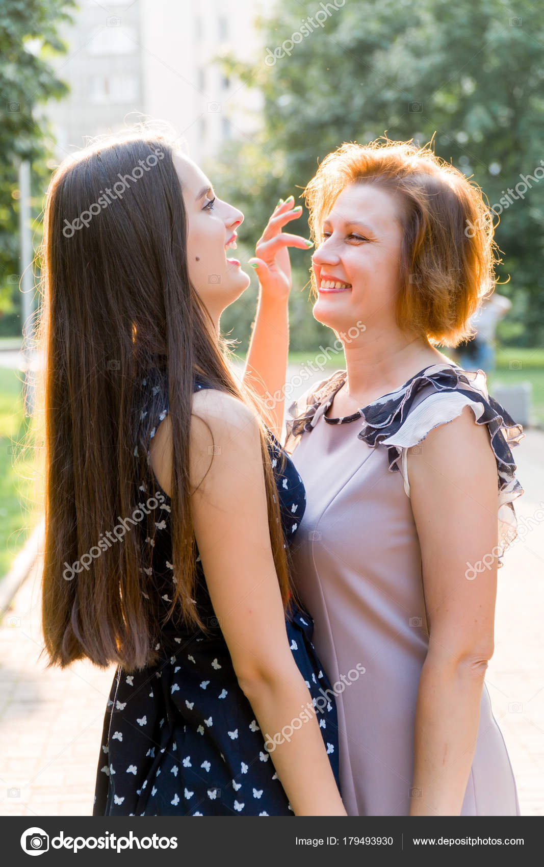 Closeup Portrait Of Adult Daughter And Mother Outdoors Pretty Brunette And Her Mom Are Looking At The Camera In The Park In Summer Photo By Sashr