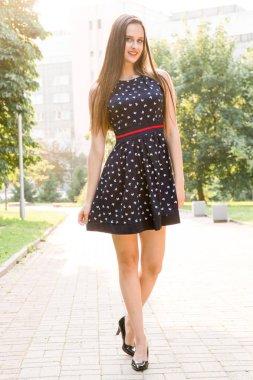 """Картина, постер, плакат, фотообои """"Молодой, красивой, привлекательной женщины в стильное платье, позирует на камеру. Она смеется, позирует для камеры, ее волосы, дует ветер, глядя очень счастлив"""", артикул 179492874"""