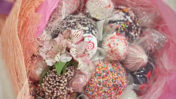 Strauß mit Lilien und Süßigkeiten, Bonbons auf dem Tisch in der Nähe von dem Kuchen. Panarama