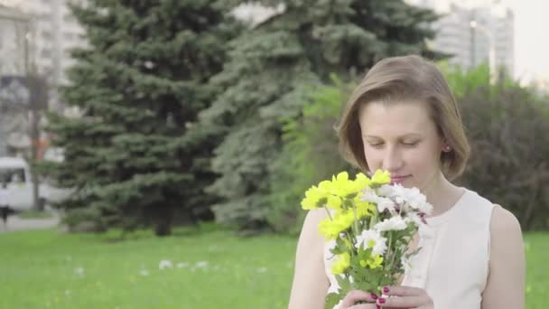 Portrait of a pretty young woman sniffing a bouquet. Beautiful woman inhales the fragrance of flowers