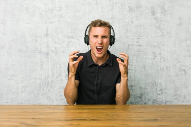 Young caucasian man listening to music with headphones upset screaming with tense hands.